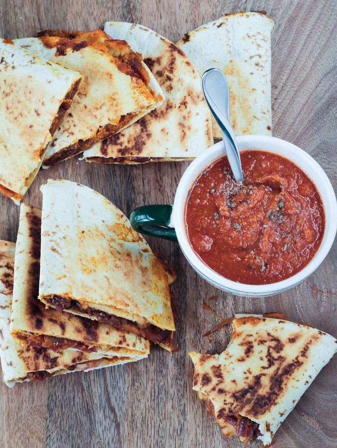 Several slices of vegan quesadilla spread out on a wooden board surrounding a cup of tomato soup.