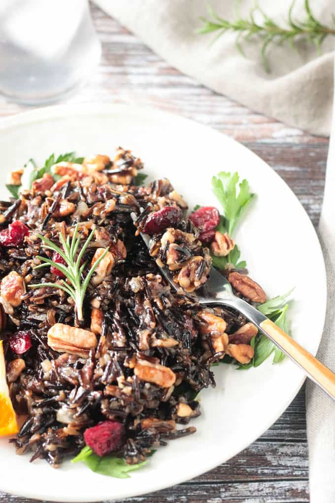 A forkful of wild rice salad lies on the side of a plate full of more salad.