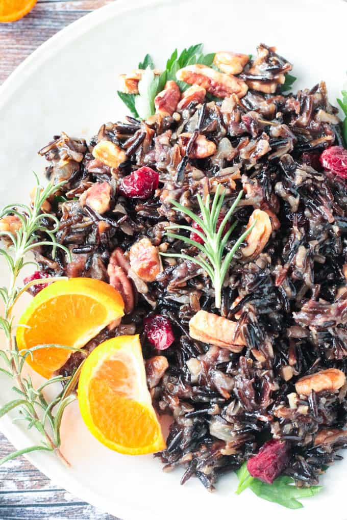 Wild Rice Salad with pecans and cranberries. A sprig of rosemary on top and two orange segments on the side.