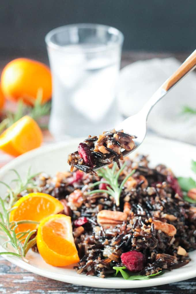 Forkful of wild rice salad being lifted off a plate.