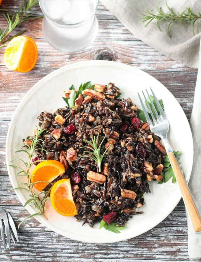 Wild Rice Salad on a plate with two orange segments and a sprig of rosemary. A fork lies on the plate to the side.