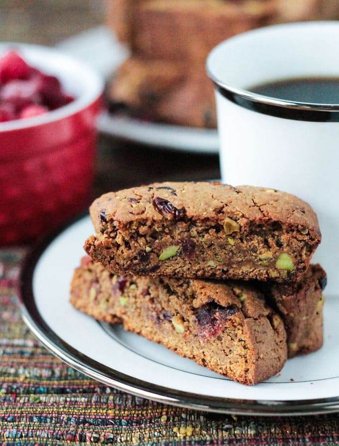 Stack of three Whole Wheat Cranberry Pistachio Vegan Biscotti on a plate with a cup of coffee.