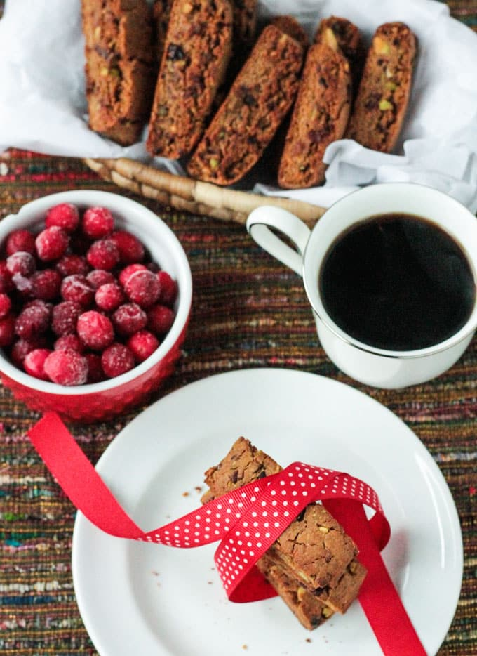 Basket Cranberry Pistachio Biscotti next to a bowl of fresh cranberries, cup of coffee, and a plate of three stacked biscotti tied in a red ribbon.