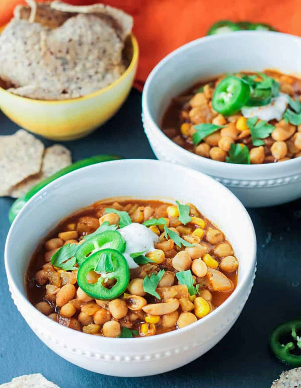 Two white bowls of hearty chickpea & white bean soup.