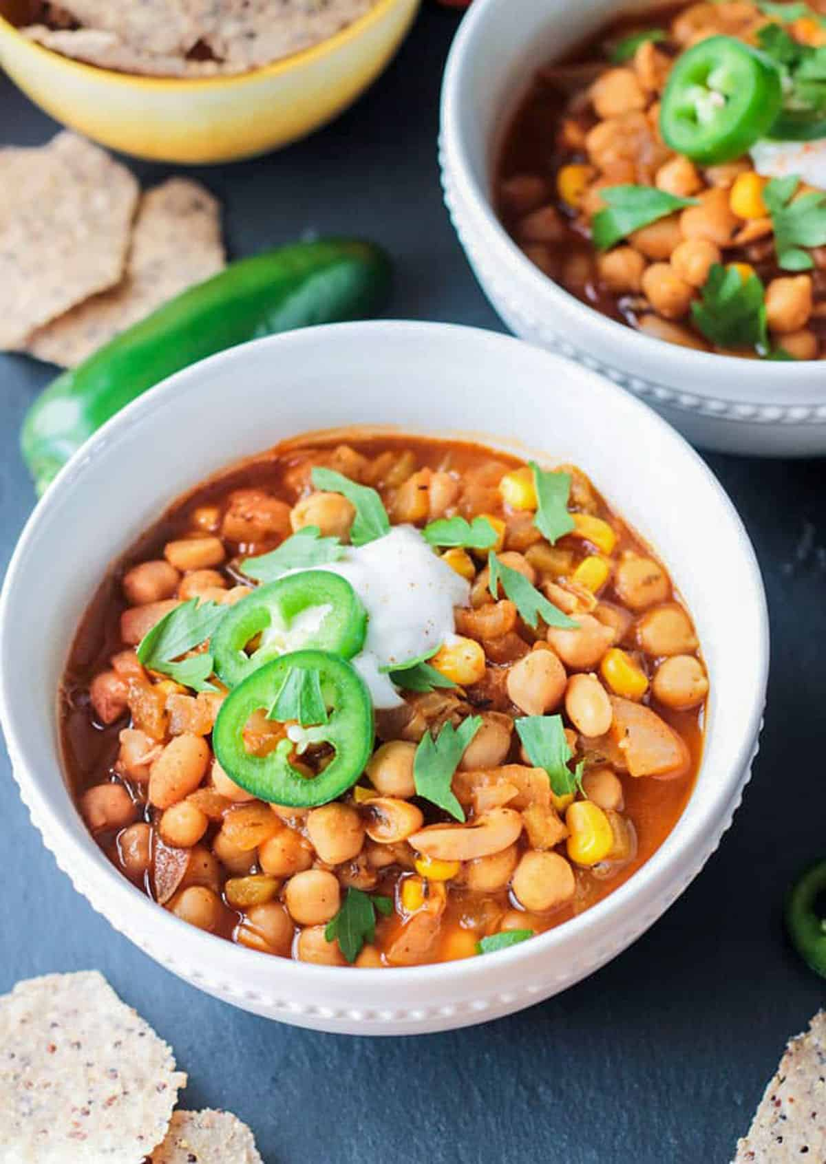 Vegan white chili with chickpeas topped with jalapeño slices.
