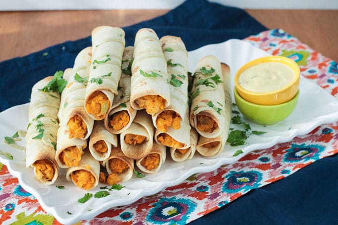 Buffalo Chickpea Artichoke Taquitos stacked pyramid style on a white plate next to a dipping bowl of ranch dressing.