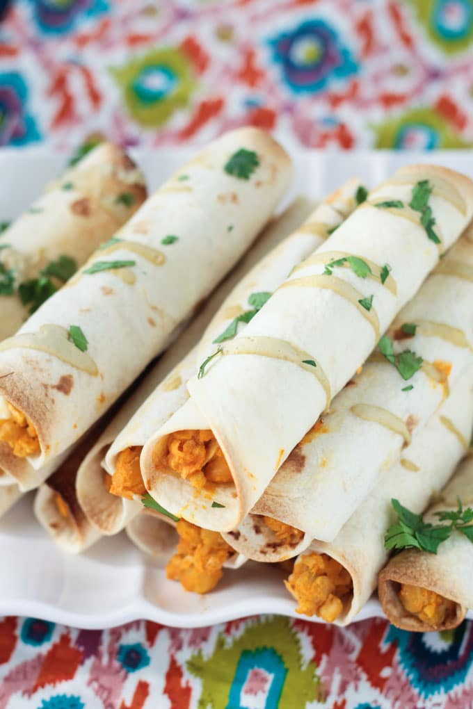 Close up shot of Baked Vegan Taquitos drizzled with dairy free ranch dressing and sprinkled with fresh parsley.