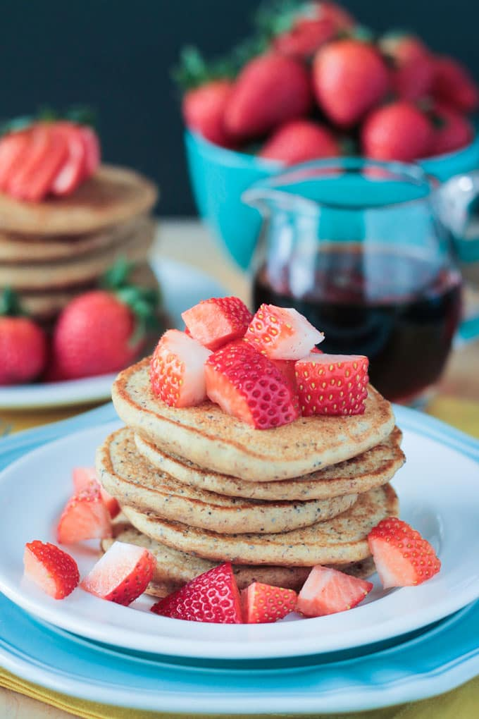 Stack of Lemon Poppyseed Pancakes with fresh cut strawberries on top and on the plate. Small glass jar of maple syrup and a blue bowl of fresh whole strawberries in the background.