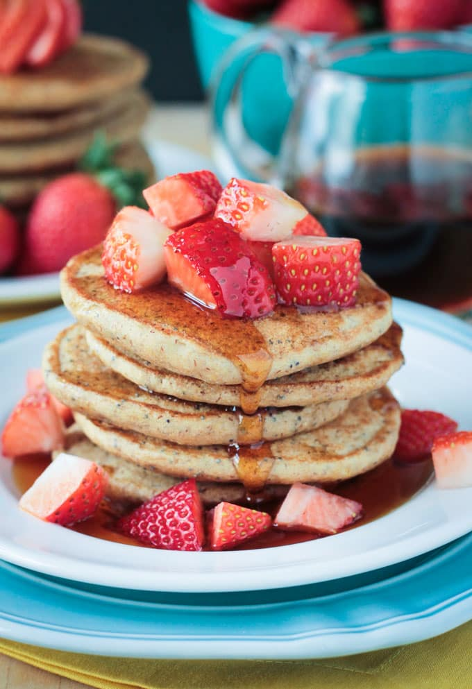Stack of Lemon Poppyseed Pancakes topped with fresh chopped strawberries and a drizzle of maple syrup.