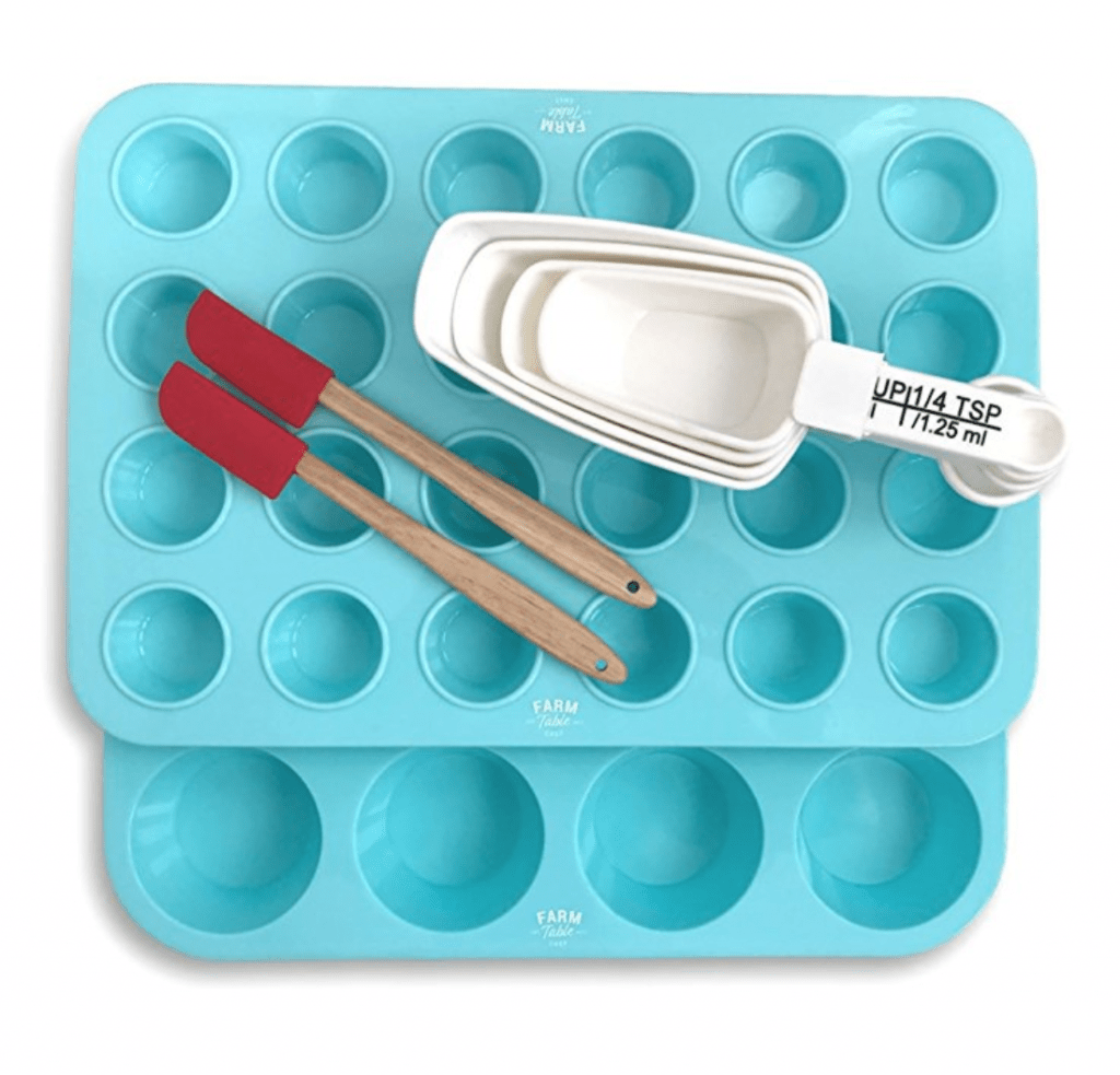 Farm Table Chef blue silicone muffin pan, blue mini muffin pan, white measuring cups, and two small red silicone spatulas.
