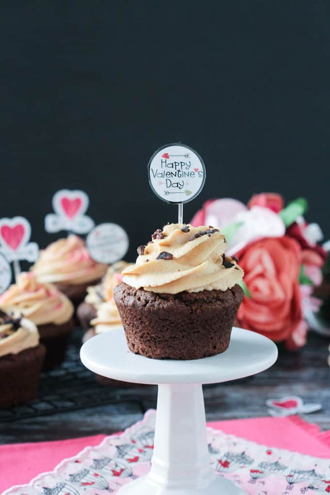 Chocolate Peanut Butter Cupcake w peanut butter frosting and cocao nibs on a individual cupcake stand. Happy Valentine's Day cupcake topper sticking in the center of the frosting.