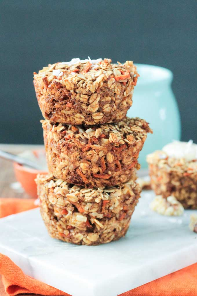 Front view of a Stack of 3 Carrot Cake Baked Oatmeal muffins on a white marble slab
