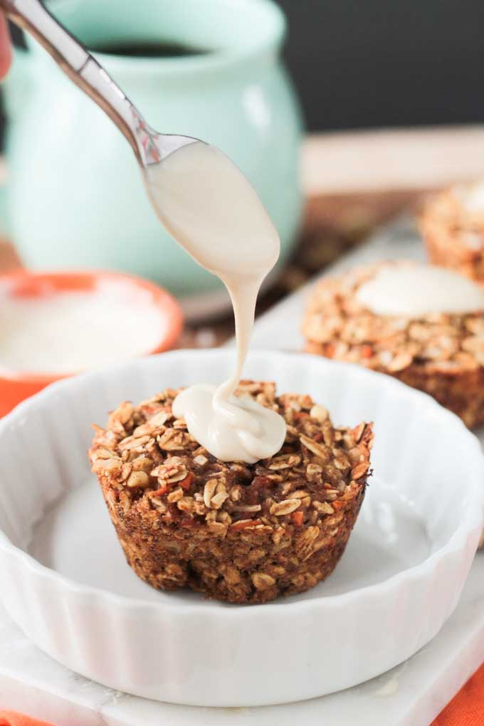 Sweet cashew cream frosting being spooned on a Carrot Cake Baked Oatmeal muffin on a white dish.