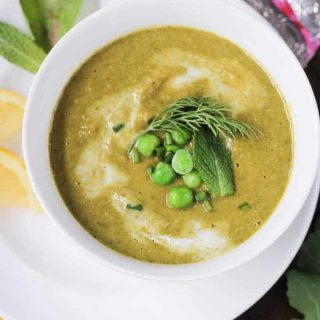 Bowl of creamy green vegetable soup garnished with peas & a sprig of dill.