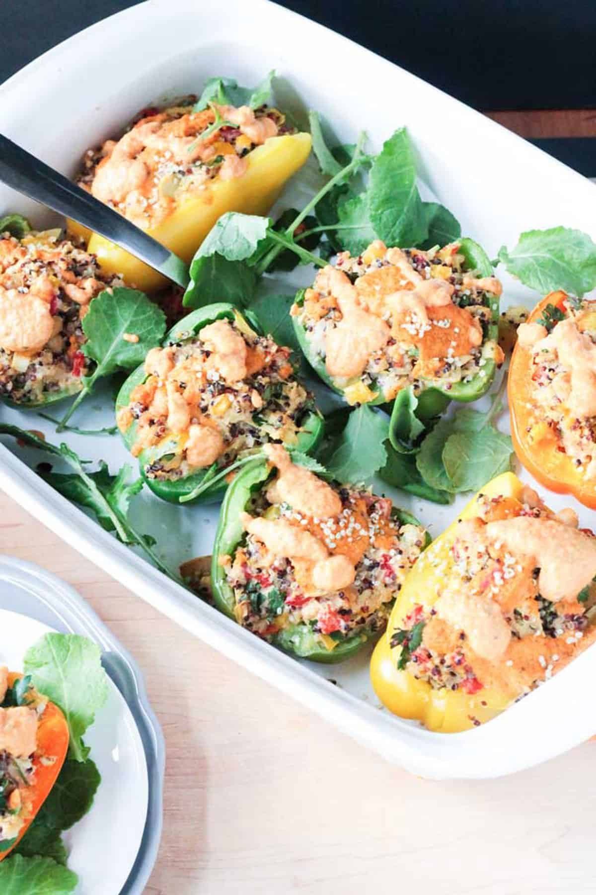 White casserole dish of stuffed peppers on top of fresh baby kale.