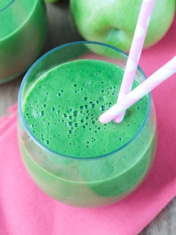 green drink in a glass with two pink straws
