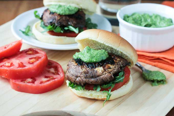 Portobello slider topped with pesto and sitting on a bed of arugula and fresh tomato slices all on a burger bun. Tomato slices next to the burger.
