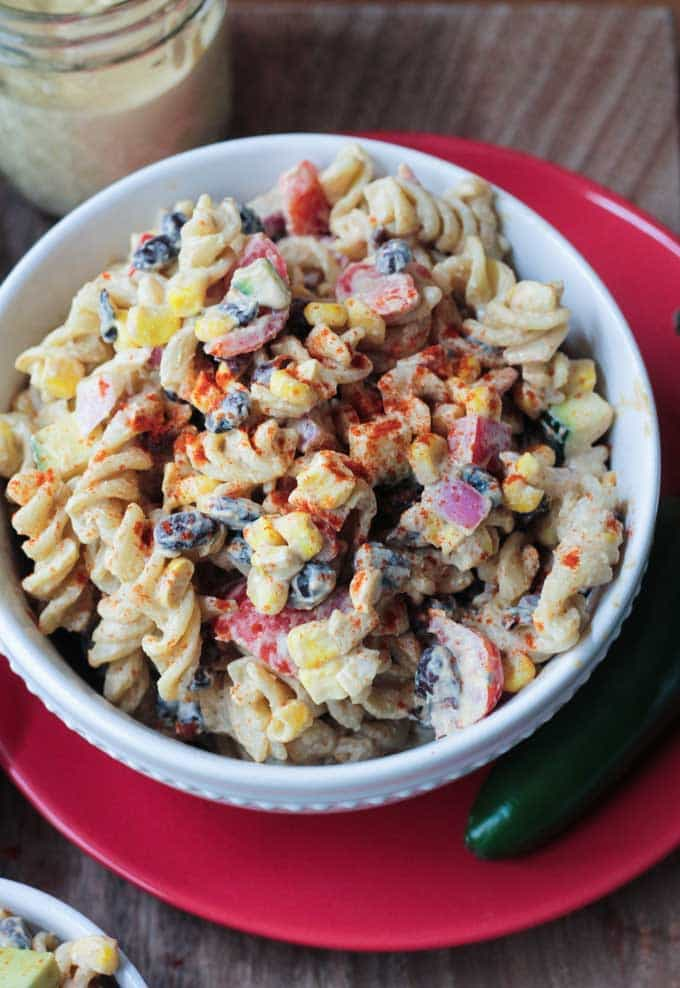 Southwest Black Bean Pasta Salad in a white bowl on a red plate. One jalapeño on the plate next to the bowl.