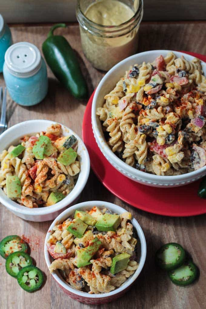 Three bowls of Southwest Black Bean Pasta Salad. Fresh jalapeño slices on the table around the bowls. Glass jar of southwest ranch dressing behind next to a full jalapeño and a salt shaker.