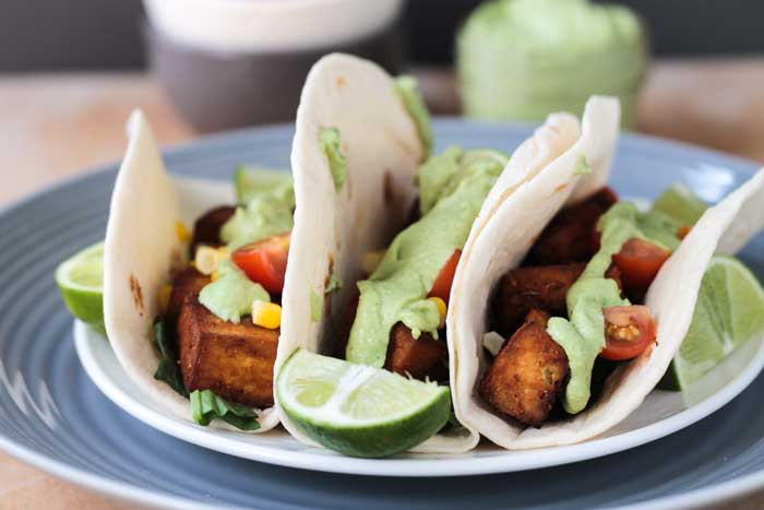 Three Baked Tofu Tacos in flour tortillas and topped with creamy avocado sauce on a gray plate. Lime wedges scattered about the plate.