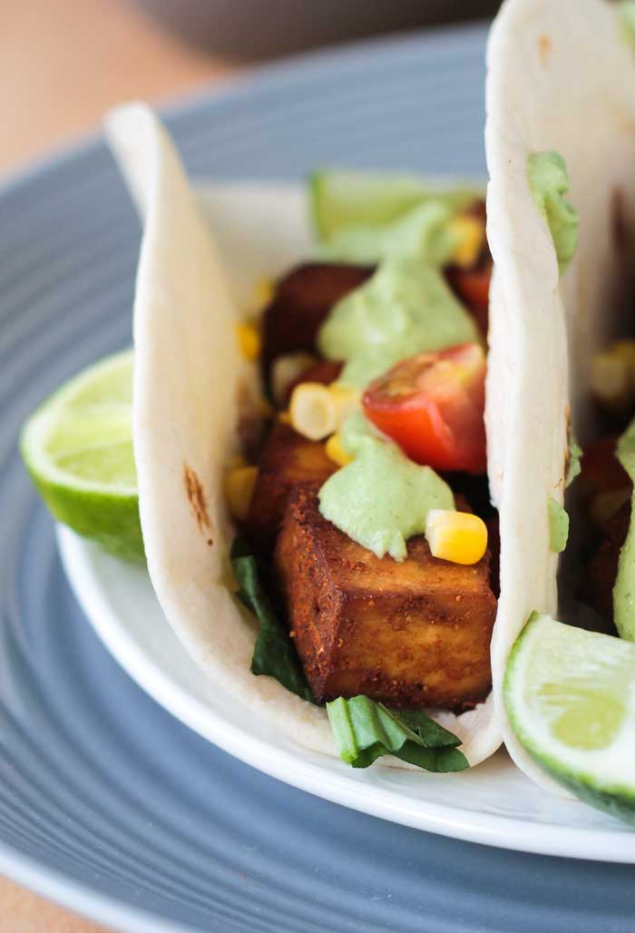 One baked tofu taco topped with cherry tomatoes, corn kernals, and creamy avocado sauce.