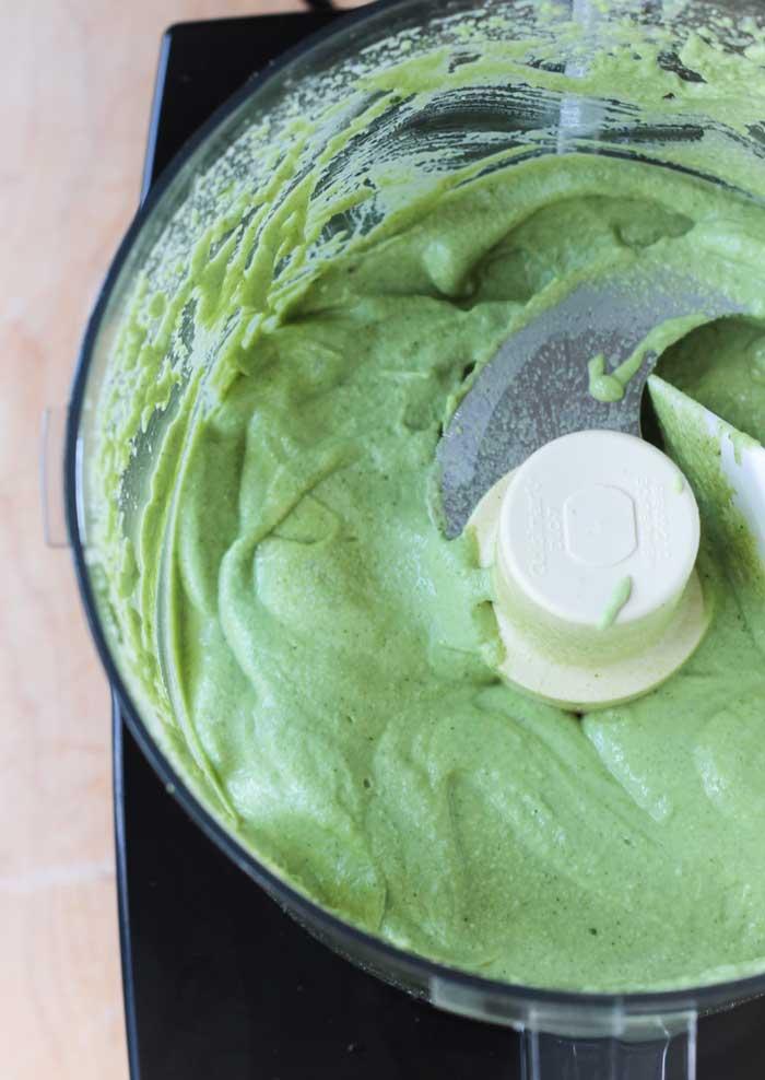 Creamy smooth avocado cilantro sauce in a food processor.