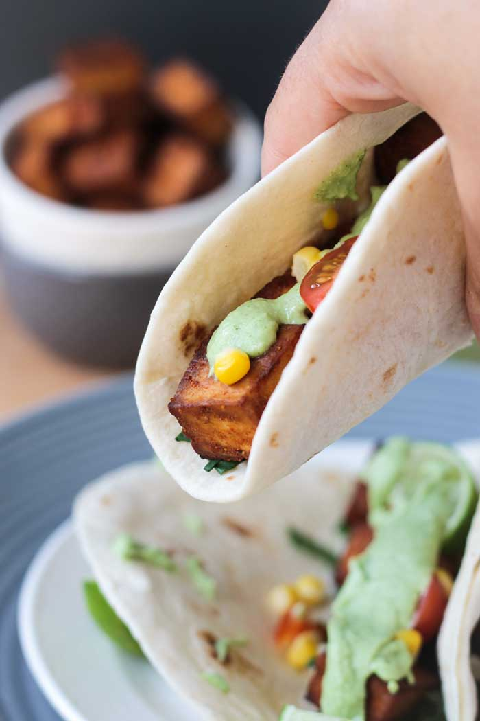 Hand holding one taco with baked tofu and a creamy cilantro sauce.