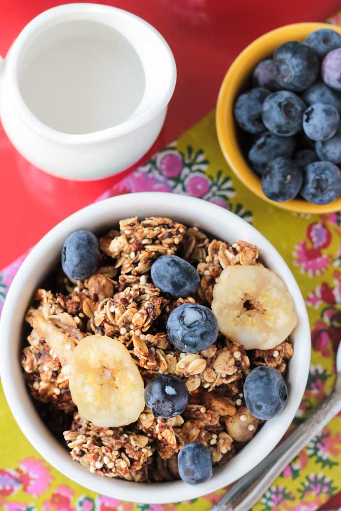 Bowl of Banana Bread Granola, small bowl of blueberries, cup of milk.