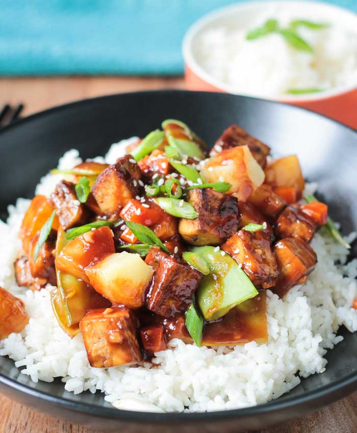 Bite size chunks of baked tofu, pineapple, snow peas, carrots, and scallions over white rice in a black bowl.
