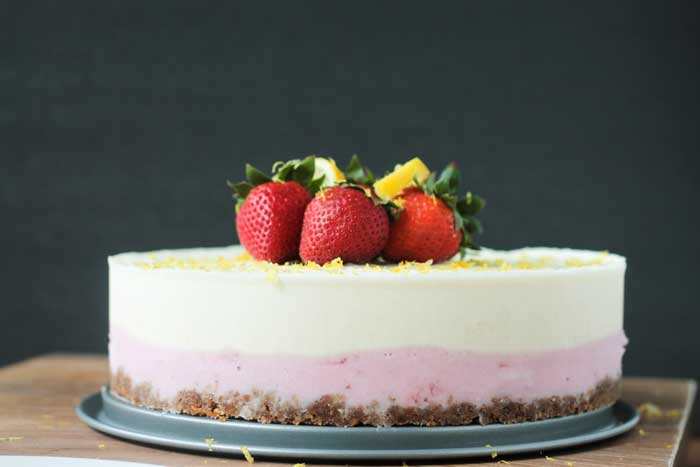 Ice cream cake with layers of pretzel crust, strawberry, and lemon and garnished with fresh strawberries.