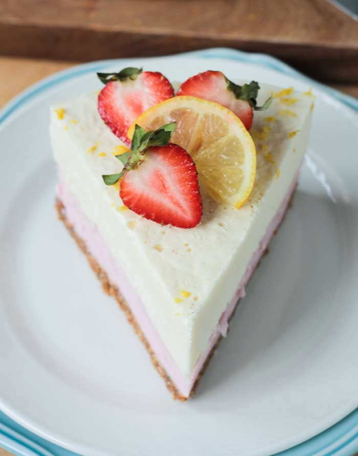One slice of Strawberry Lemonade Ice Cream Cake garnished with fresh strawberries and a lemon slice.