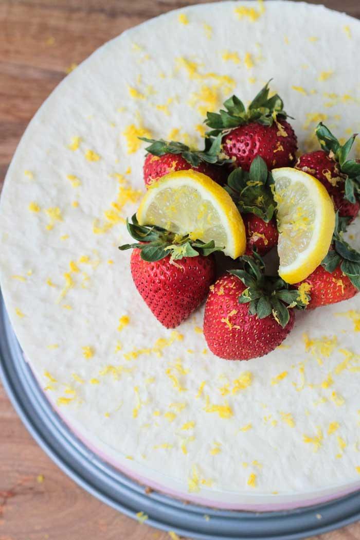Fresh strawberries, lemon slices, and lemon zest sit atop a lemon ice cream cake.