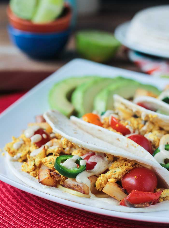 Folded tortilla filled with scrambled tofu, roasted potatoes, peppers, tomatoes, and a drizzle of ranch dressing. A bowl of lime wedges and a stack of tortillas in the background.