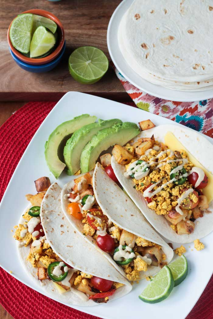 A white plate with three scrambled tofu & roasted potato breakfast tacos. Avocado slices and lime wedges on the side.