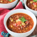 Chunky vegetable quinoa soup in a white bowl.