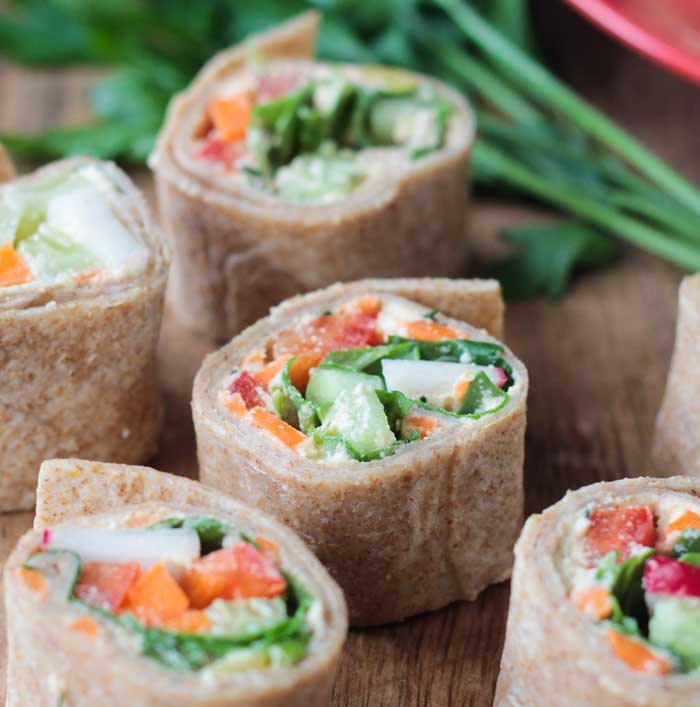 5 tortilla rollups with vegetable filling on a wooden tray with a bunch of fresh parsley in the background.