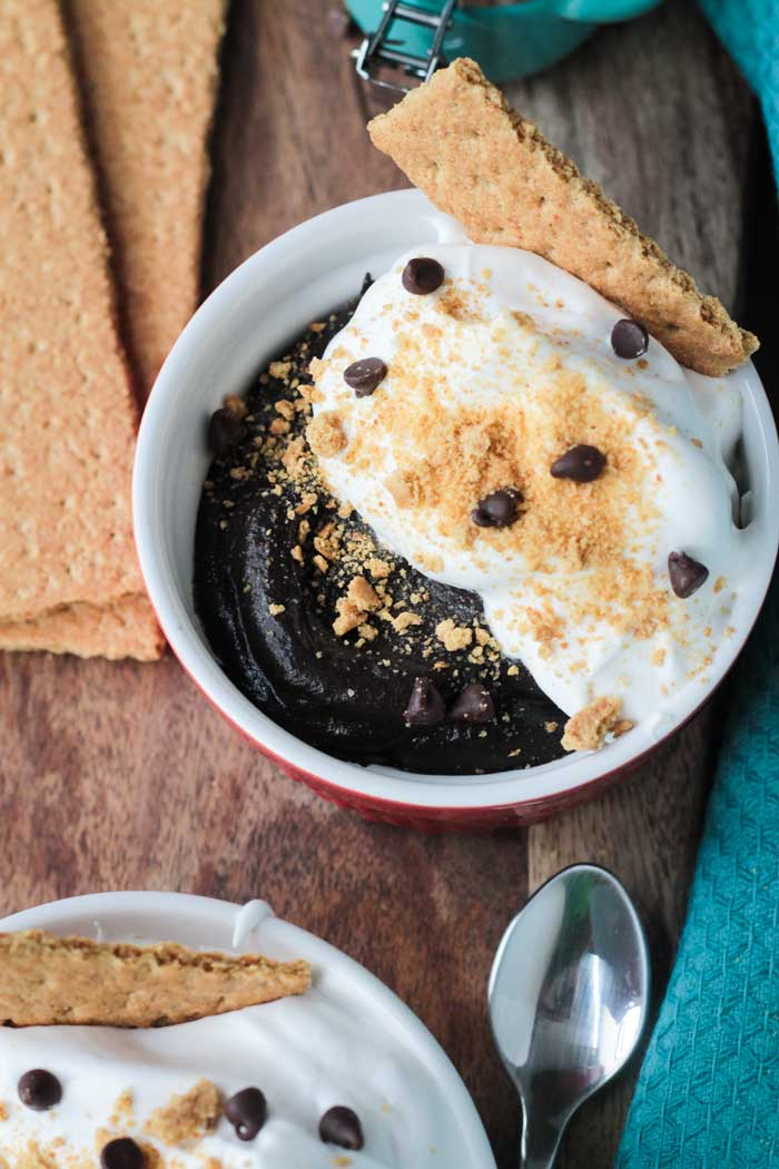 Chocolate pudding bowl topped with whipped topping, graham cracker crumbs and mini chocolate chips. One graham cracker square dunked in the side.