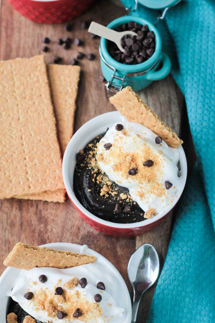 S'mores Pudding Bowl with dairy free whipped topping in small red/white bowl. Graham crackers next to the bowl. Small blue bowl of mini chocolate chips behind. Blue dish cloth to the side.