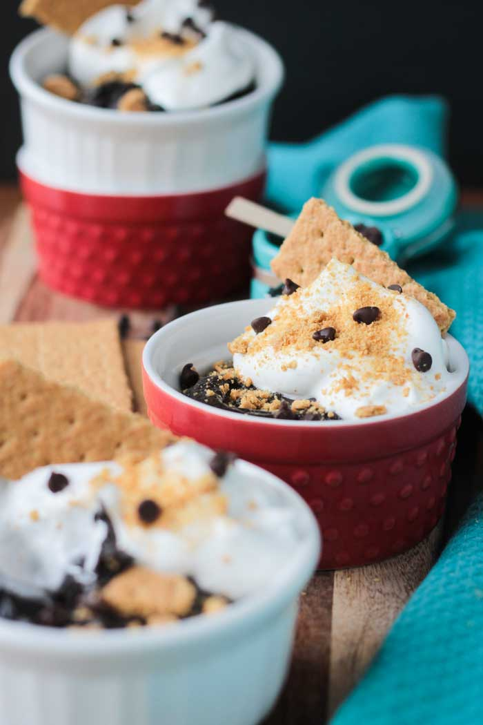 Two bowls of s'mores pudding - white bowl in front, red bowl behind. Two more stacked bowls behind - red one on bottom is empty, white one on top also filled with pudding.