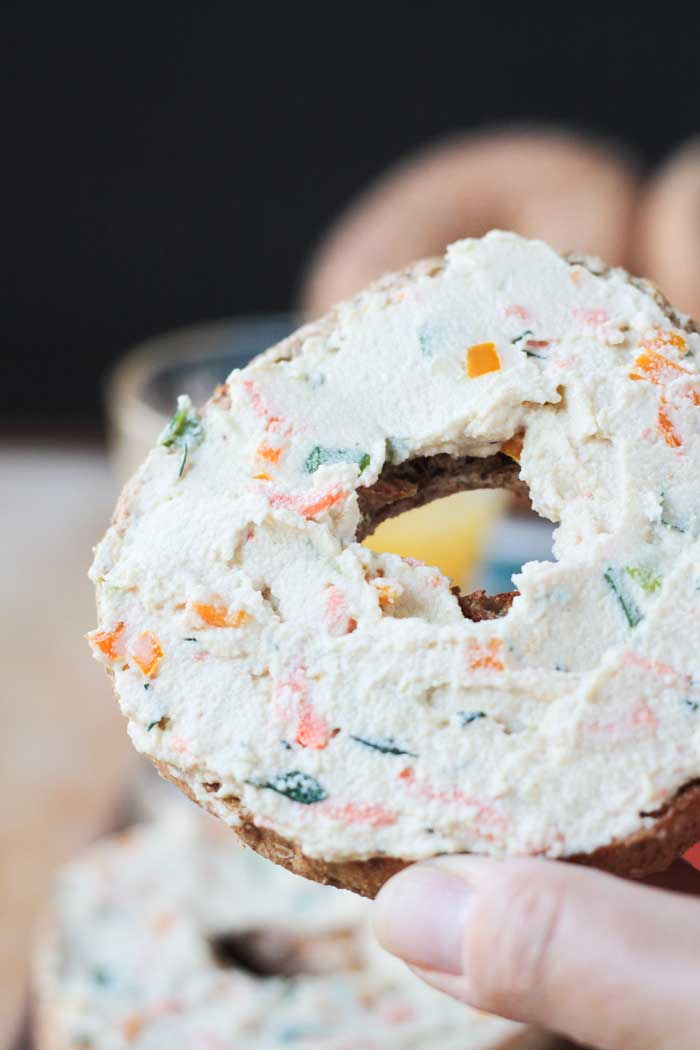 Hand holding a whole wheat bagel spread with veggie cream cheese.