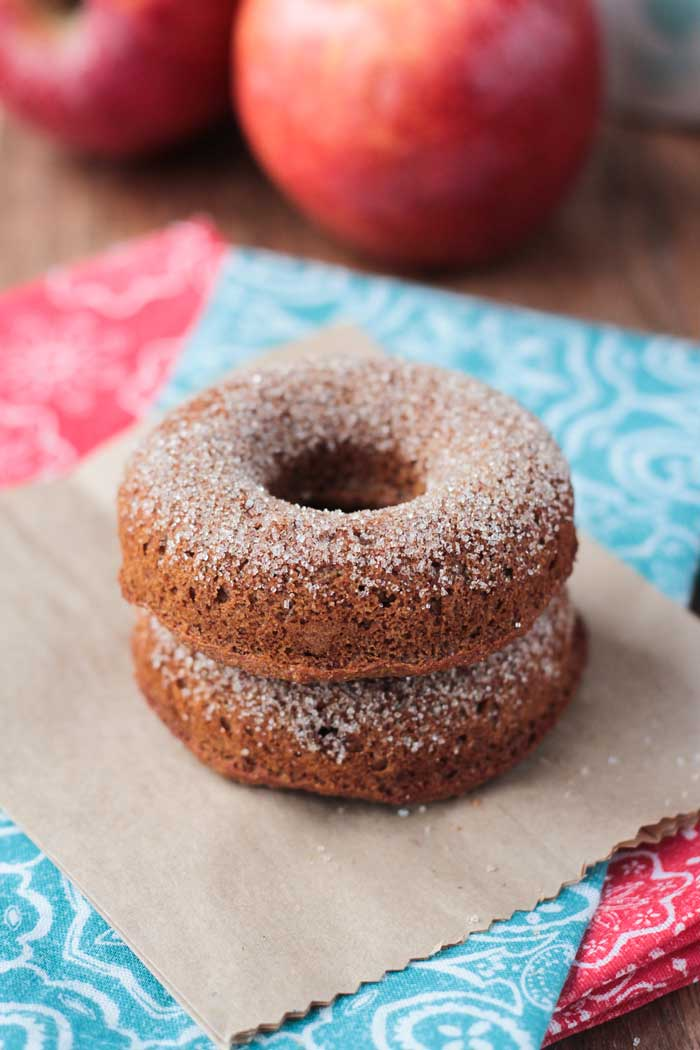 Two Baked Apple Cider Donuts stacked and dusted in cinnamon sugar.