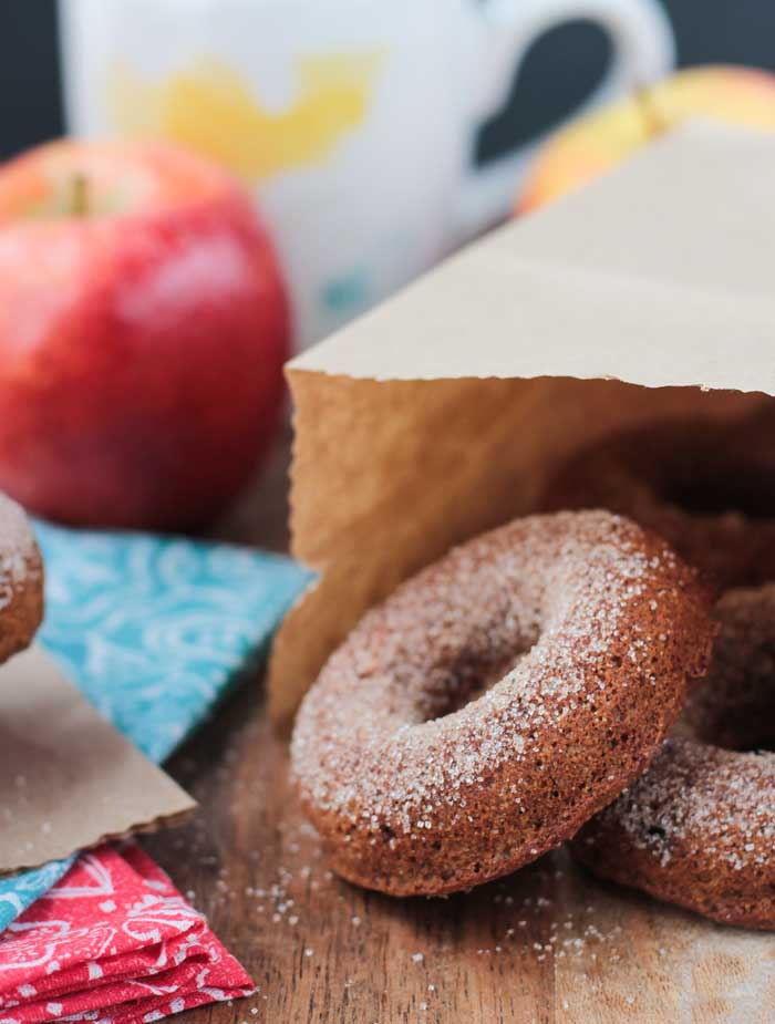 A brown paper sack on it's side on a table. Apple Cider Donuts spilling out of the bag.