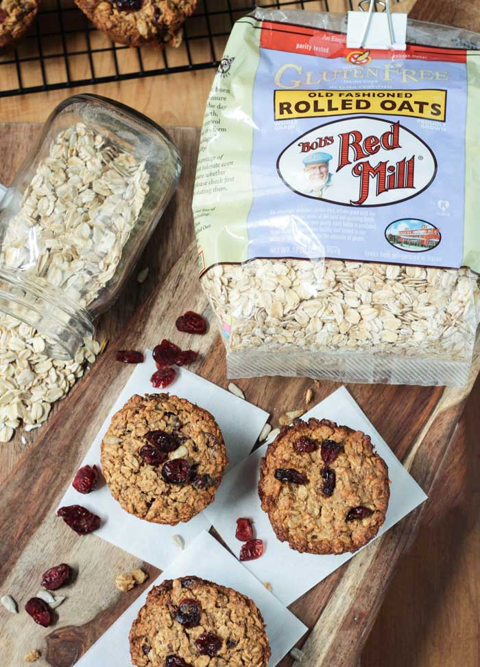 Three Cranberry Oatmeal Muffins on a wooden cutting board. Bag of rolled oats behind next to a jar lying on it's side with oats spilling out.