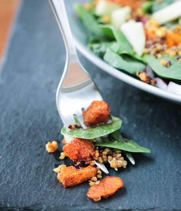 A bite of quinoa spinach salad with butternut squash on a fork.