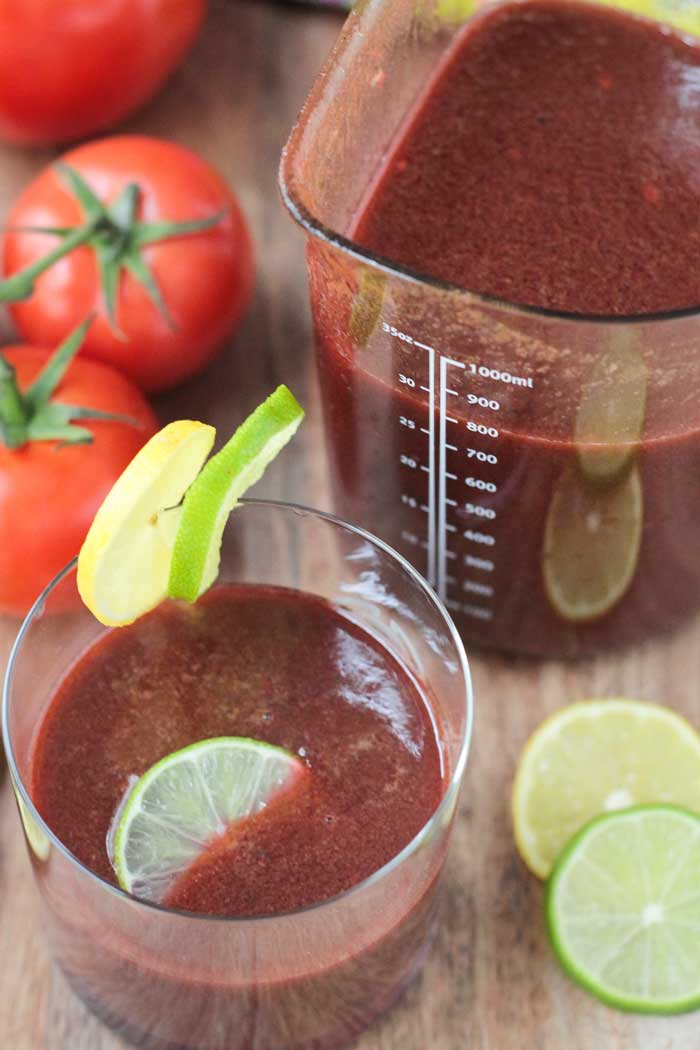 Spicy Tomato Juice in a glass. Lime and lemon slices next to the glass. Pitcher or more juice behind.