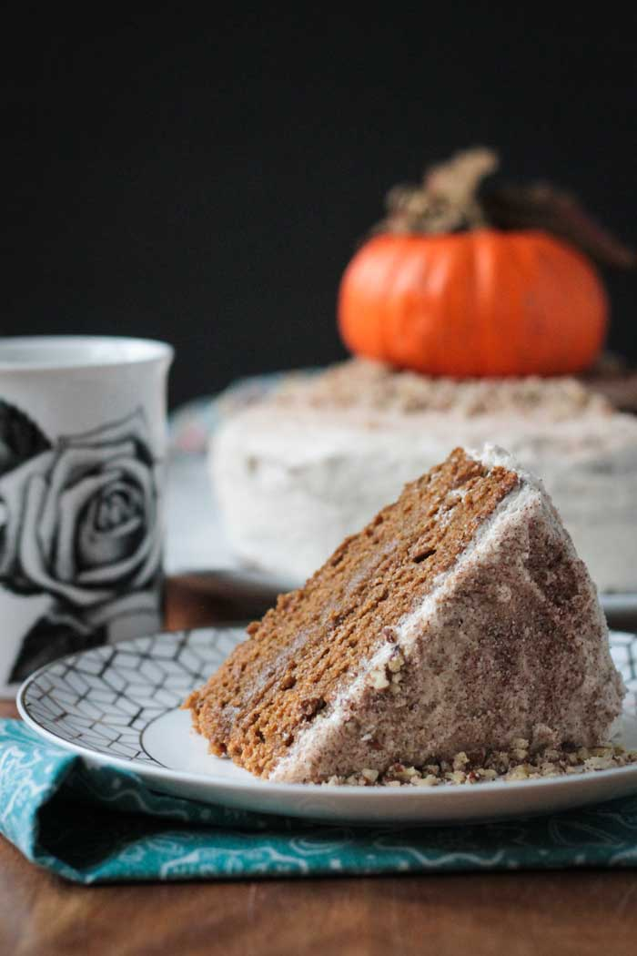 A slice of Chai Spiced Pumpkin Layer Cake on a plate in front of the rest of the cake. Coffee mug behind.