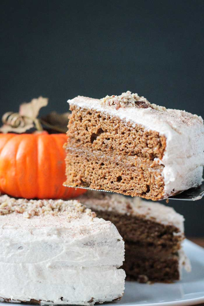 A slice of Chai Spiced Pumpkin Layer Cake being lifted up on a spatula.