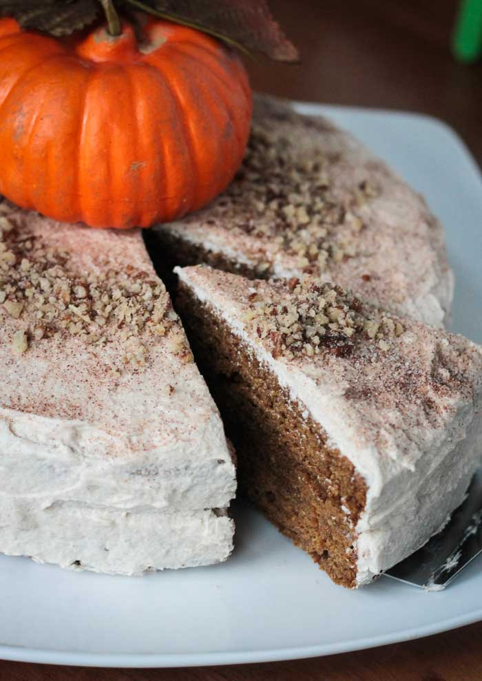 A slice of cake being pulled from a Chai Spiced Pumpkin Layer Cake. An orange decorative pumpkin on top of the cake.