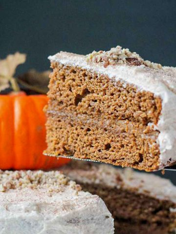 Slice of pumpkin layer cake being lifted from a whole cake.