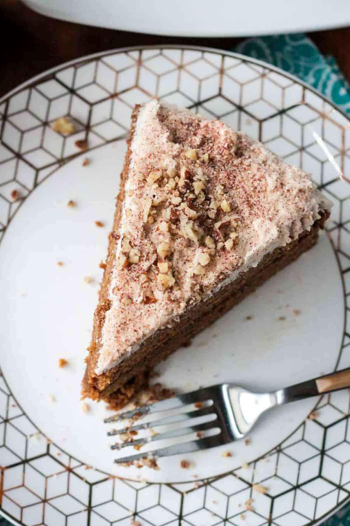 Overhead view of a slice of frosted cake sprinkled with chopped nuts.